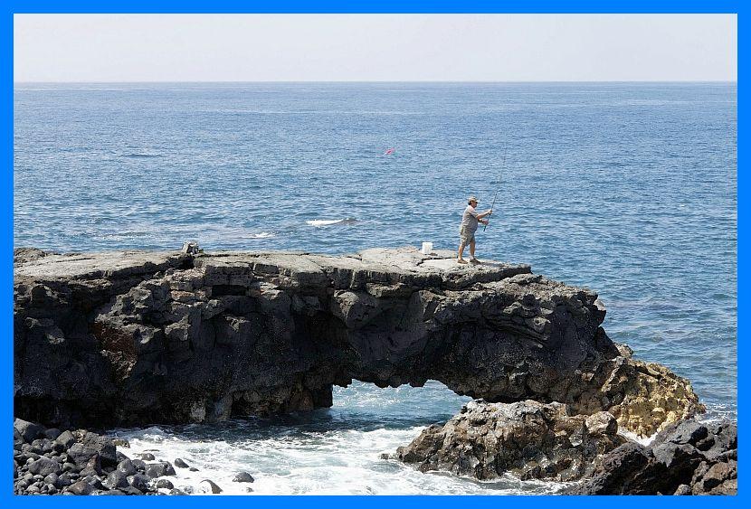 Ein Mann beim Angeln auf Felsen im Meer.